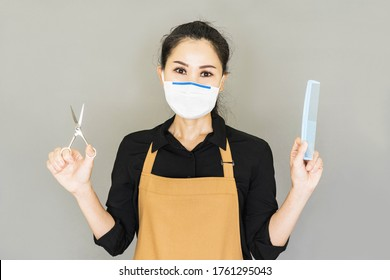 barber in medical face mask with stubble in shirt having scissors, tools, equipments, comb in hands looking at camera, reopening of the place after the quarantine isolated on grey background