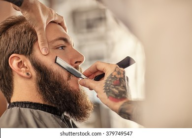 Barber with old-fashioned black razor shaving bearded man
