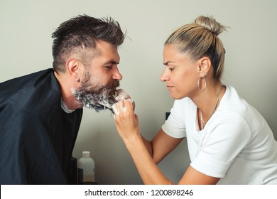 Barber paints beard and mustache in black color of hipster man in barbershop. Hairstylist hairdresser washing customer beard - man relaxing in hairdressing beauty salon. Cleaning beard Barbershop.