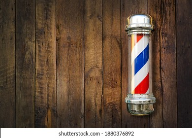 Barber pole. Barbershop pole on a wooden background with copy space. - Shutterstock ID 1880376892