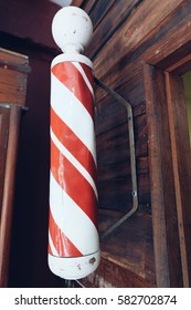 Barber pole outside a small business retail outlet,The red and white stripes represents bandages and blood.