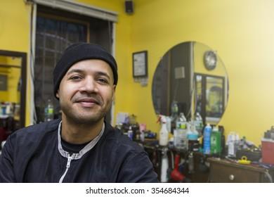 Barber posing in his shop.
