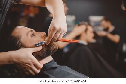Barber process shaving razor bearded hipster man in barbershop.