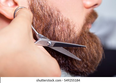 Barber with scissors shaving bearded man