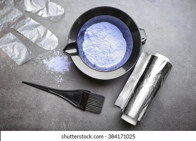 Barber set with hair dye, foil and brush on grey background