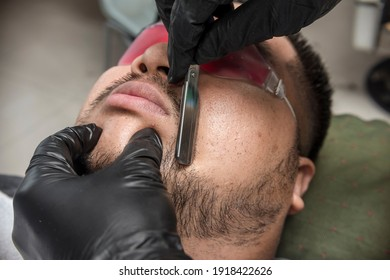 A barber shapes an asian man's beard and sideburns with a stainless razor. Professionally done facial hair styling at a barbershop or salon.