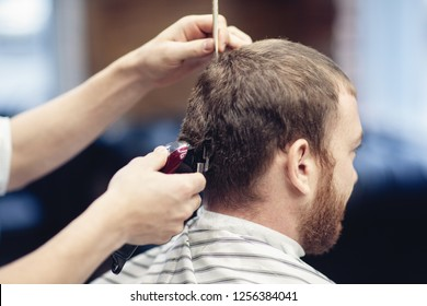 Barber shaves the client's head with a trimmer.