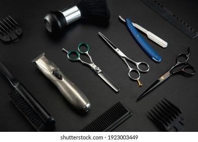 Barber shop equipment set isolated on black table background. Close up sccissors, comb, brushes, razors, professional tools of hairdresser. Professional occupation, art, self-care concept. Magazine.