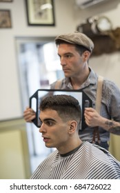 Barber shop, man cuts person hair and looking mirror