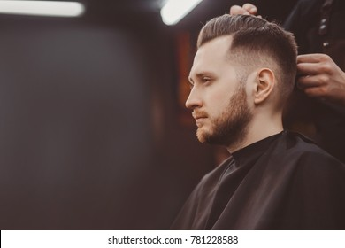Barber shop. Man with wife in barber's chair, hairdresser Barbershop styling his hair
