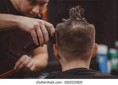 Barber shop. Master cuts hair and beard of men in barbershop, hairdresser makes hairstyle for young man