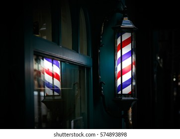 Barber shop pole by the entrance lights up in the dark.