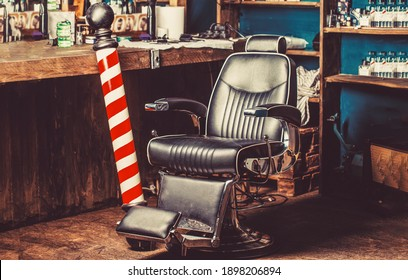 Barber shop pole. Logo of the barbershop, symbol. Stylish vintage barber chair. Hairstylist in barbershop interior. Barber shop chair. Barbershop armchair, barber shop for men.