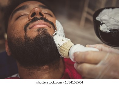 Barber shop pro spreads white shaving foam with professional brush on clients face for accurate shave.Young black man get his unshaven beard cut into shape in barbershop. Male beauty treatment concept