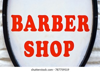 A Barber Shop sign with red letters and a white background