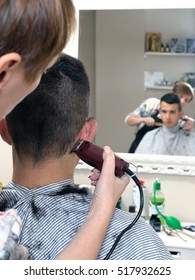Barber shop that performs the haircut of a young boy with electric clippers.