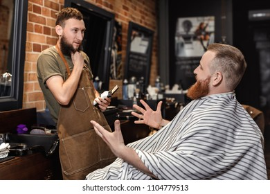 Barber talking with bearded man in barber shop
