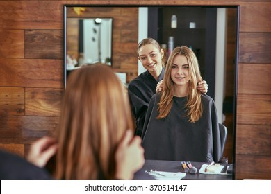 Barber talks to the young beautiful girl in a hair salon