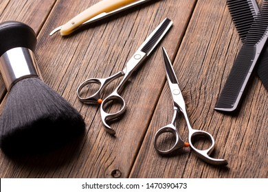 Barber tool on a wooden table. Scissors, comb for hair and a razor close-up. Hairdressing tool kit. Scissors and other tool barber. Barber set.