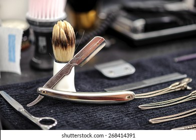Barber tools. Close-up of elegant old brush with white handle for shaving and range of old-fashioned straight razors on a barbers table
