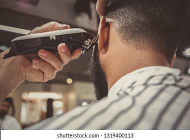 Barber trim hair with clipper on young unshaven black man in barbershop studio.Professional hairdresser cut hair with electric shearer machine on African guy. Male beauty treatment process
