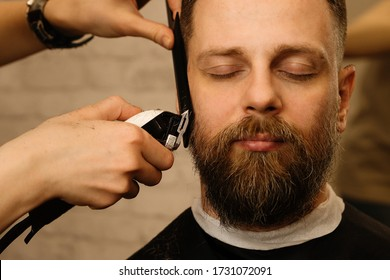 Barber trimming beard of male customer with electric razor at barbershop. Man with beard and moustache getting stylish trendy hair shaving, with hair clipper and comb. Close up.