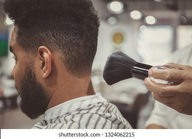 Barber uses shaving brush on clients neck to spread talcum powder for shaving neck with razor in barbershop .Male beauty treatment concept