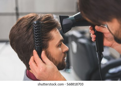Barber using hairdryer at beauty salon