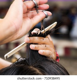 barber using scissor for cutting black hair of the young man