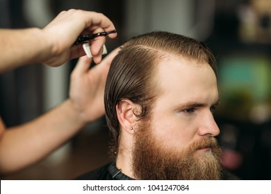 Barber using scissors and comb in barbershop