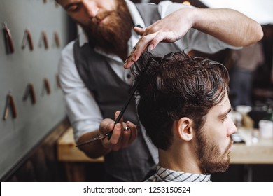Barber using scissors and comb. Man with beard getting haircut in barber shop. Modern hair salon concept.