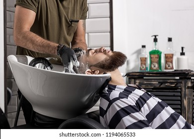 Barber washes the man's hair in a barbershop