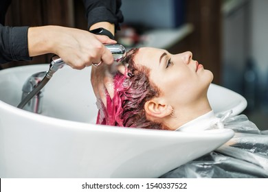 Barber is washing the girl pink hair in the beauty salon. Hands of hairdresser washes woman hair in sink at beauty salon close up.