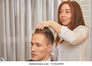 Barber woman and her client. Young male in hair salon.