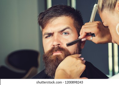 Barber woman shaving client's beard in barbershop or beaty salon. Portrait of male client shaving his beard at salon. Barber at work. Man at barbershop. Handsome man with beard in barbershop.