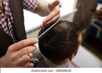 Barber at work. Close up cutting hair.