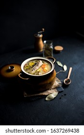Barberry soup, Polish sauerkraut soup. Served in a clay pot. Dark background .