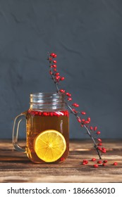 Barberry tea with lemon in a glass jar cup, branches with berries on a wooden table. A healing drink.