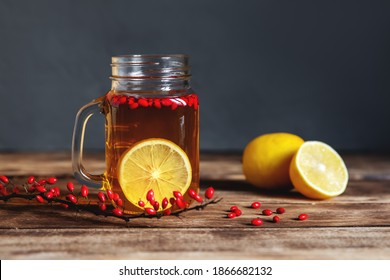 Barberry tea with sliced lemon in a glass jar cup, branches with berries on a wooden table. A healing drink.