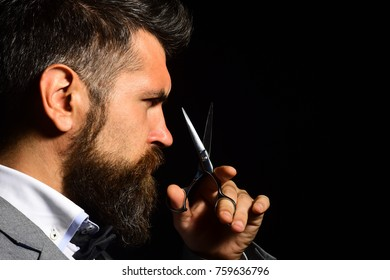 Barbershop advertising concept. Macho in formal suit cuts beard and moustache. Man with long beard holds steel scissors. Businessman with strict face isolated on black background.