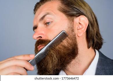 Barbershop. Bearded man with barber comb. Salon for men. Professional beard care. Hairdresser. Bearded man with comb. Barber-shop.