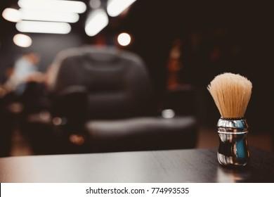 Barbershop. Brush for shaving beard along with bowl, blurred background of hair salon for men, barber shop