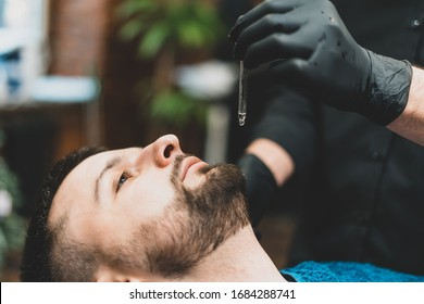Barbershop. The client in the master's chair in the barbershop, the barber applies oil and cosmetics to the client's beard. Male beauty shop. Healthy lifestyle and beauty