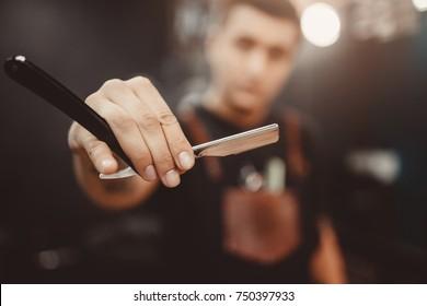 Barbershop. Close-up of barber holds razor for shaving his beard
