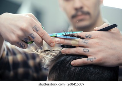 Barbershop. Closeup of barbers tattooed hands combing hair making haircut to a male client