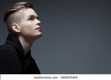 Barbershop concept. Portrait of a young fashionable man in trendy sweater posing over gray background and looking up. Perfect haircut. Hipster style. Studio shot
