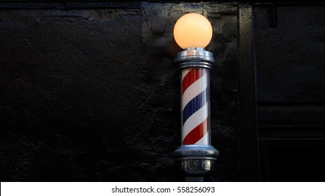 Barbershop pole against black brick wall.