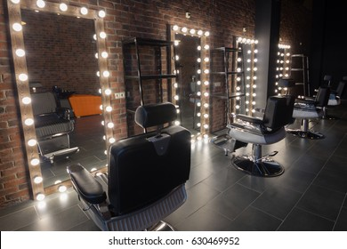 Barbershop room with places for hairdresser and make-up artist work - seats and mirror with illumination