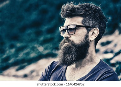 Barbershop and style concept. Man with beard and mustache on strict face, nature background, defocused. Bearded man wears modern sunglasses. Hipster with beard looks confident while standing outdoors.