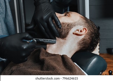 BARBERSHOP THEME. BARBER IN BLACK RUBBER GLOVES IS TRIMMING THE BEARD OF HIS YOUNG HANDSOME CLIENT. HE IS USING A  STRAIGHT RAZOR